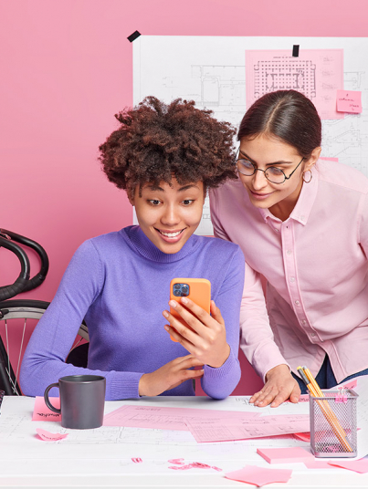 Coopeation and teamwork concept. Professional two women colleagues check newsfeed on modern cellular read email from customer work on blueprints for new house or building pose in office at desktop